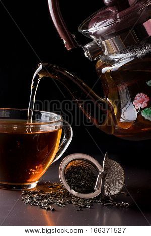 cup of tea with teapot on dark background.