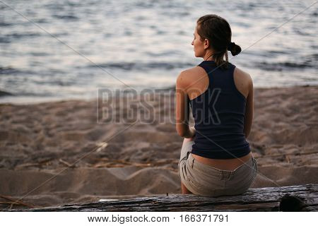 Young attractive woman enjoys sunset, sitting on big wooden beam next to water of evening lake, pleasured with warm chill evening with closed eyes