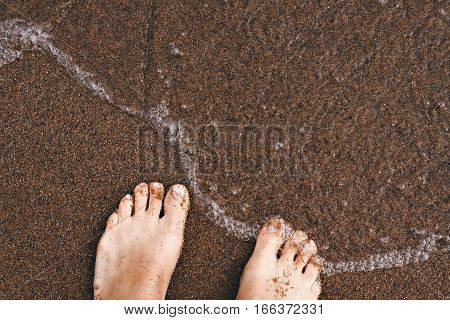 Top view of women legs toes on wet sand on lake shore