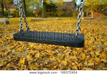 Lonely child swing on a children playground in autumn