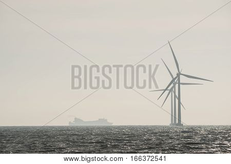 Silhouette wind turbines and ferry boat at the Baltic Sea