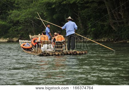 September 3 2016. Wuyishan China. Boatmen using bamboo sticks to steer the bamboo boats down the Jiuqu Xi river or nine bend river in Mount Wuyi Scenic area in Fujian province China on an overcast day.