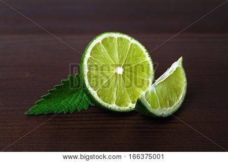 Fresh sliced lime fruits isolated on wooden background