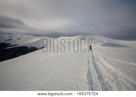 Way at the top of a snowy a mountain ridge with tourists hiking