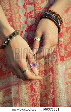 Hands in the original bracelets holding purple flowers