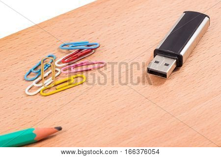various office supplies flash card for storing information a pencil for writing and drawing and paper clips for fastening papers
