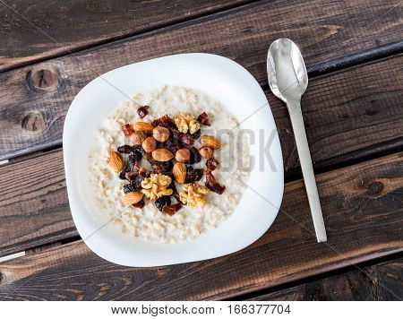 Plate of homemade oatmeal porridge with dried plums, hazelnuts, almonds, walnuts and dates on old dark grey rustic wooden table with spoon. Hot and healthy food for Breakfast.