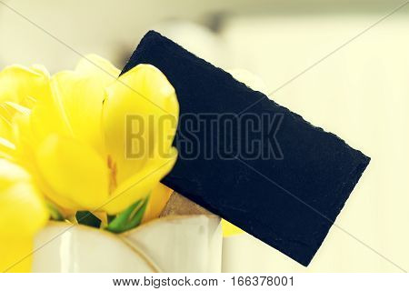 Beautiful Fresh Spring Yellow Tulips in Vase on bright background. Spring easter or Mother's Day Concept.