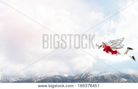 Young cheerful man with megaphone flying high in sky