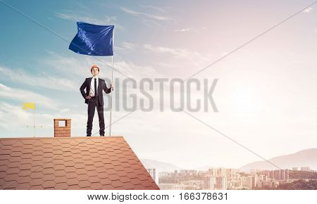 Businessman standing on house roof and holding blue flag. Mixed media