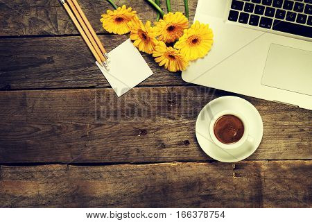 Working space or working place with laptop pencils and flowers on old wooden vintage table. Top view with copy space. Spring or business concept.