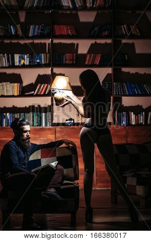 young couple of handsome bearded man sitting on armchair in library reading book and pretty cute girl or woman in black lingerie with sexy buttocks and body holding lamp