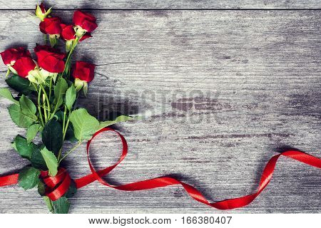 bouquet of red roses flowers with red ribbon over rustic wooden background with copy space. top view. vintage toning