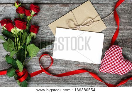 blank white greeting card and envelope with red roses flowers and handmade heart on rustic wooden background. top view. valentines day background