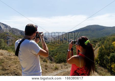 Two photographer standing against the backdrop of panoramic view of the mountains
