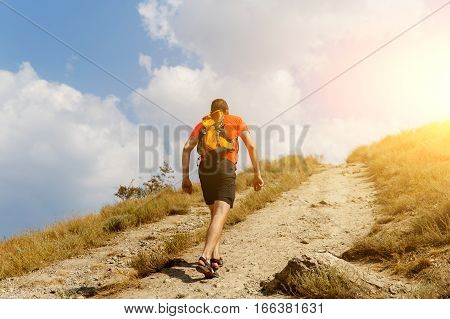 Traveler goes up steep hill in summer day