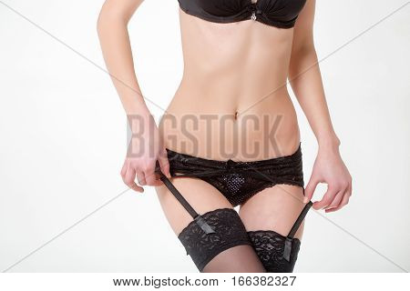 female body of young pretty woman or cute sexy girl in fashionable black erotic stockings panties and bra isolated on white background