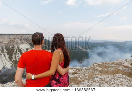Loving couple standing back against backdrop of beautiful mountains summer