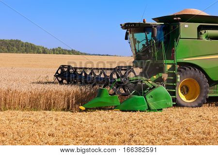 Green grain combine harvester working in field