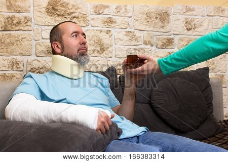 An injured man is served a glass of tea