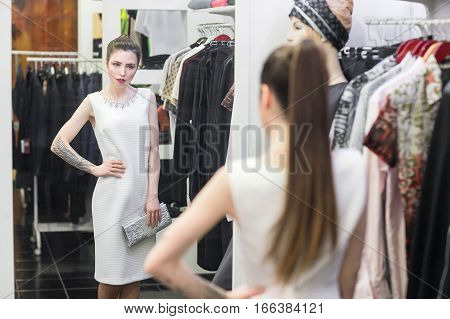 Beautiful young woman in a fitting room at a clothing store he sees his reflection in the mirror.