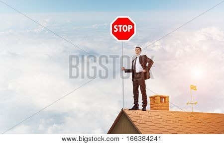 Businessman standing on house roof and holding prohibition sign. Mixed media