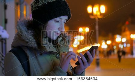Young pretty woman using smartphone in the city at night. Technology, winter and holiday concept