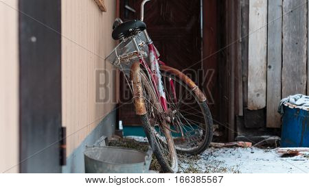 old bicycle standing outside the house under the snow
