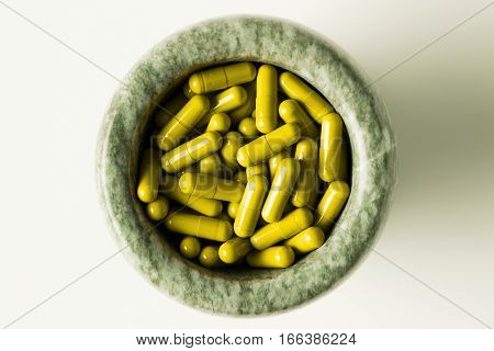 Yellow Capsules And Orange Pills With Mortar Pestles On White Background.