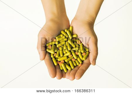 Hands Is Giving Yellow Capsules And Orange Pills On White Background.