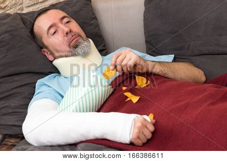 Injured man lies lazily alone on a couch