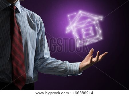 Hand of businessman showing house glowing sign in palm
