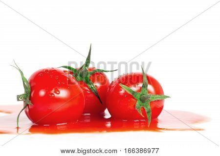 Tomatoes are in tomato juice on white background. Red and ripe tomatoes.