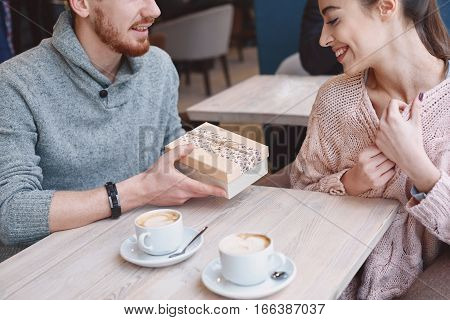 Two people, man and woman in cafe communicate, laughing and enjoying the time spending with each other. Couple in love on a date. A woman receives a gift from a man. Love story and Valentines Day concept