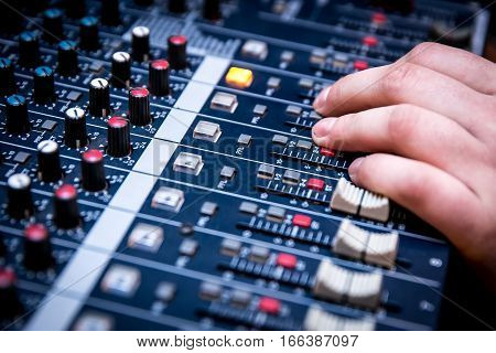 Sound manager is working on the audio mixer, preparing new mix of a song or work on live event