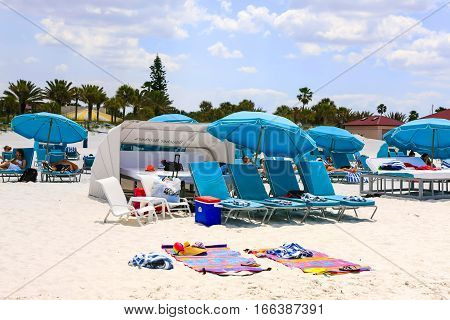 Clearwater, FL - April 21: Blue Umbrellas, Cabanas and towels on Clearwater beach in Florida