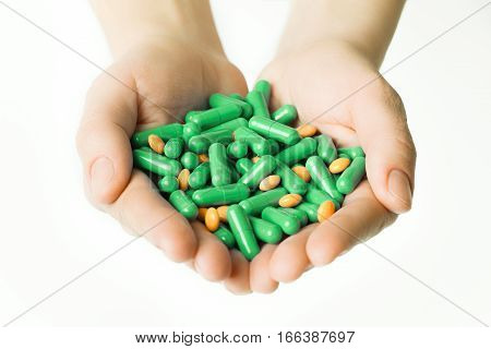 Hands Is Giving Green Capsules And Orange Pills On White Background.