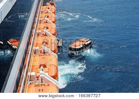 Dubronik Croatia - December 20 2007: Orange lifeboats modern boats for emergency evacuation loading for safety training from liner or ship on sunny day on blue sea background