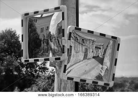Two driveway traffic mirrors on the pole in croatian village Nevidane black and white photo