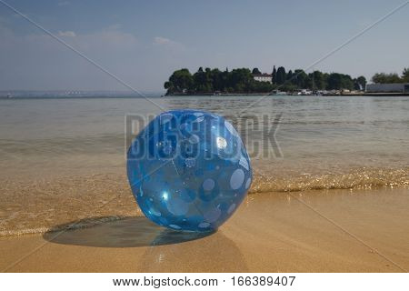 Blue beach ball on a sand beach by Adriatic sea