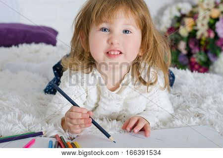 Smiling little girl drawing in bed colored pencils