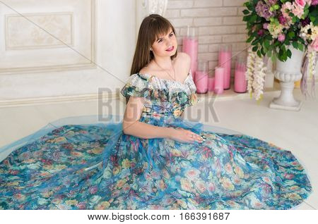 beautiful girl in a ball dress sitting on the floor against the backdrop of vintage fireplace