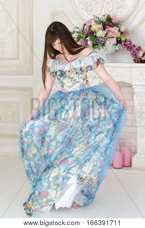 beautiful girl dancing in the ball dress on a background of vintage fireplace