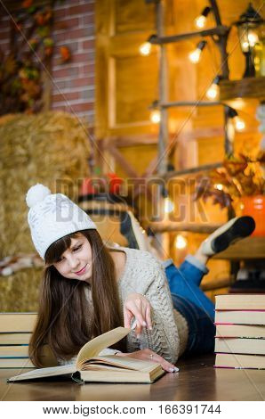Girl in a sweater and jeans lying on the floor and reading a book