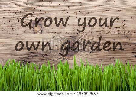 English Text Grow Your Own Garden. Spring Season Greeting Card. Bright Aged Wooden Background With Gras.