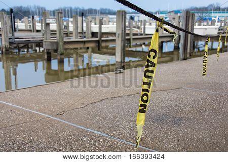 hanging yellow caution tape strip on marina walkway