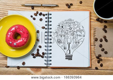Notepad with idea sketches coffee cup and pencil on wooden table