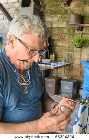 Senior Man squeezing oil color on a wood palette