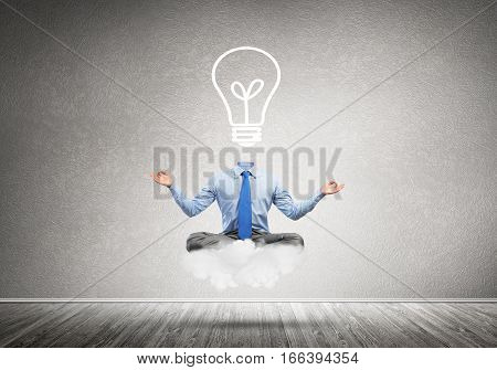 Businessman sitting in lotus pose and light bulb instead of his head