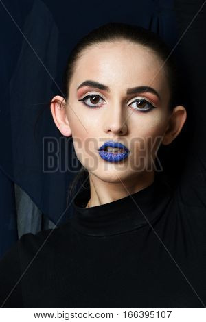 Pretty girl or beautiful woman with sexy blue lips and bright fashion makeup poses in black clothes on fabric texture background